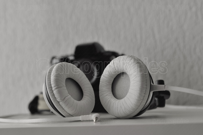Headphones and film photo camera in background