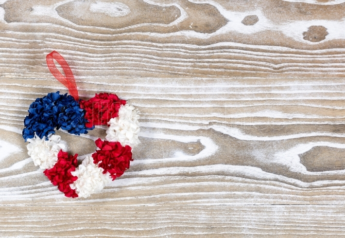 Heart wreath in USA traditional colors on white wooden boards