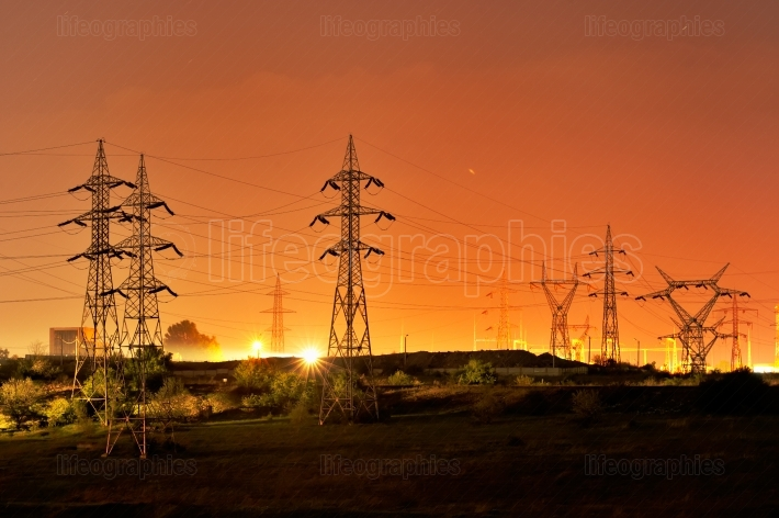 High voltage electric pillars on sunset background