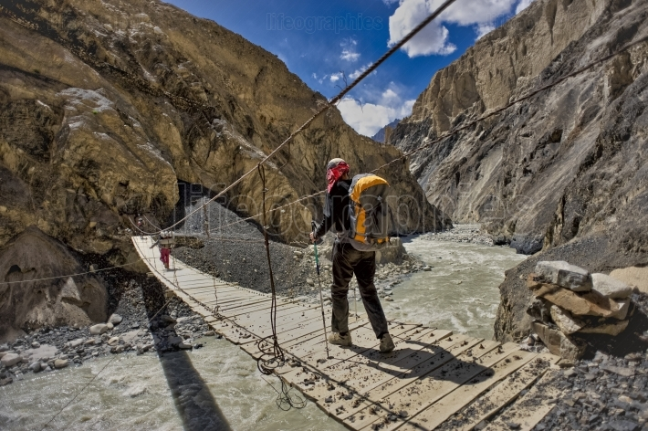 Hiker on suspension bridge from Karakoram Mountains. Shimshal, Pakistan