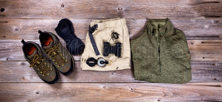 Hiking gear and clothing on rustic wooden boards