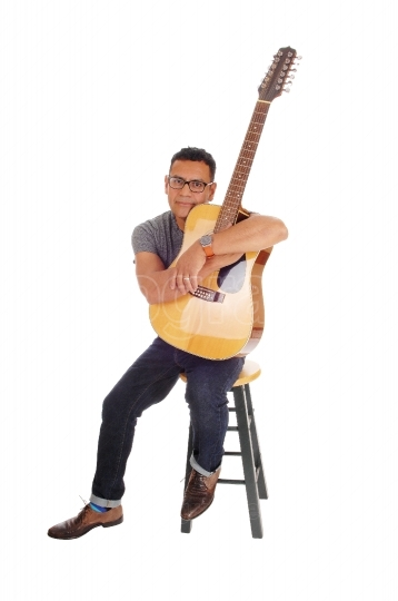 Hispanic mal sitting with his guitar.