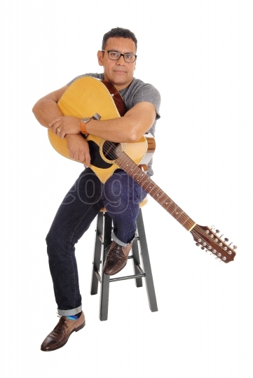 Hispanic man holding his guitar.