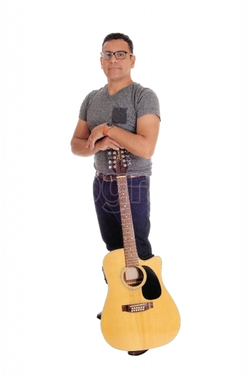 Hispanic man standing with guitar.