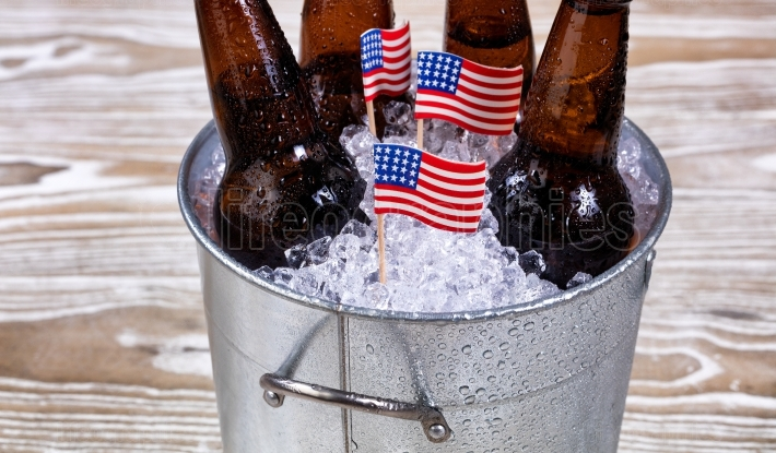 Holiday USA flags and bucket of ice cold beer on rustic wood