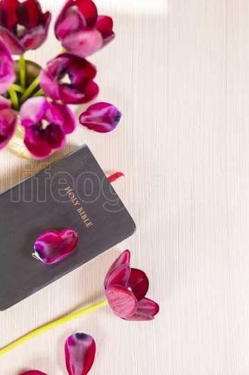 Holy Bible and flowers on wood table