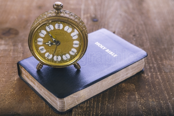 Holy Bible and old alarm clock on wood table