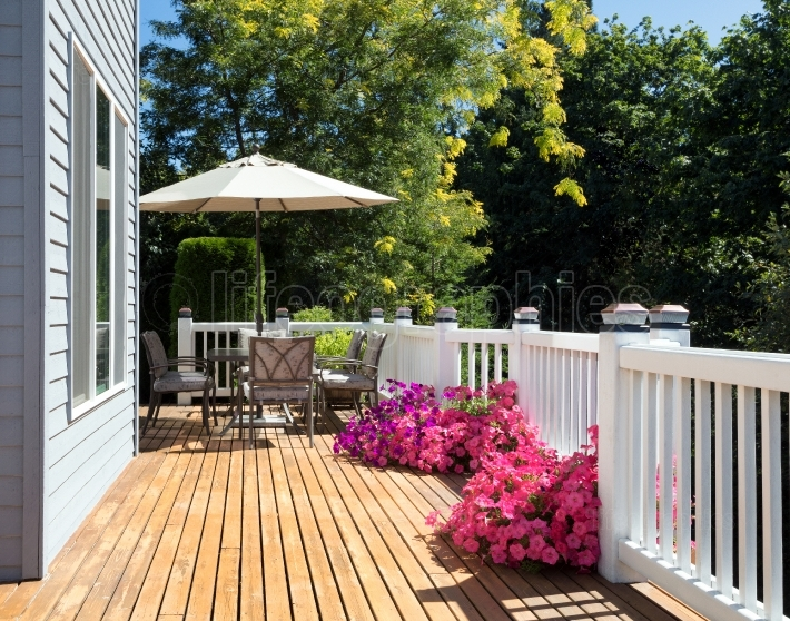 Home cedar deck during bright summer day with blooming garden of