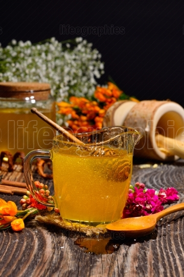 Honey and wild flowers on wooden background