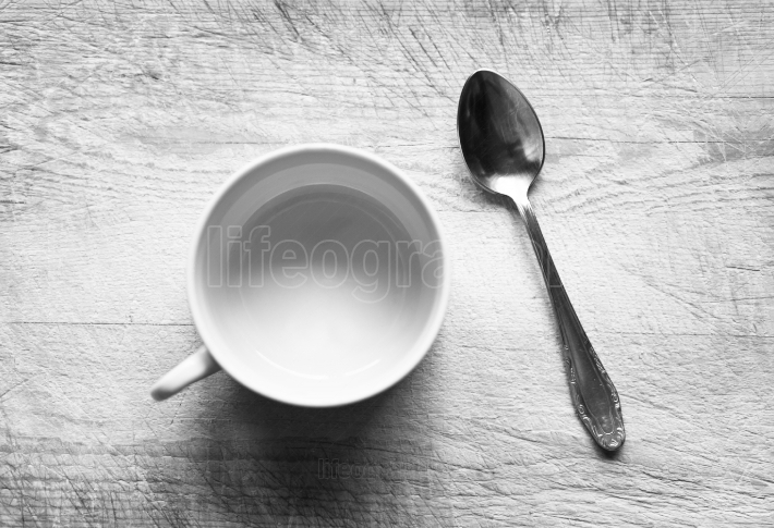 Horizontal black and white empty cup with spoon bokeh background