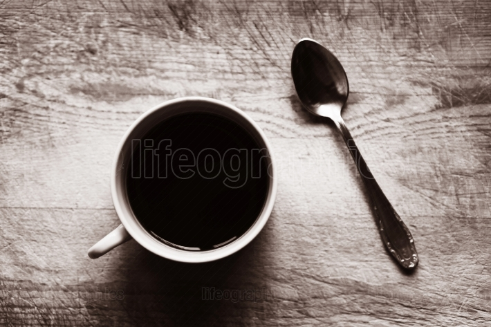 Horizontal cup with spoon bokeh sepia background