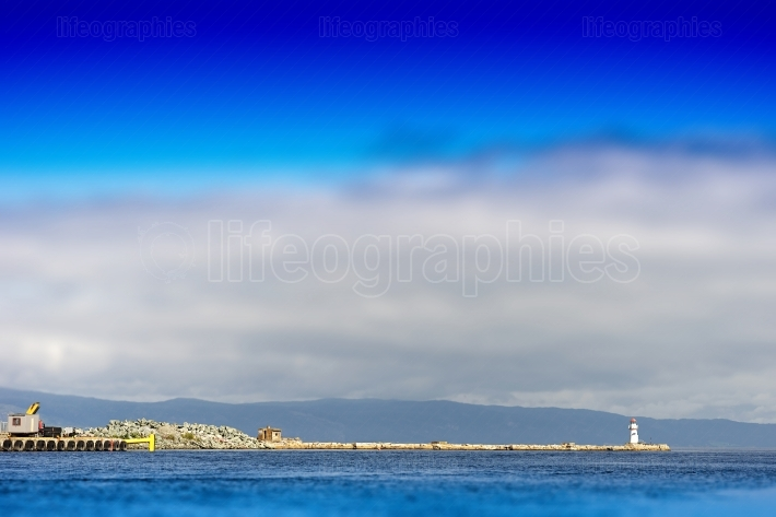 Horizontal pier with lighthouse bokeh background