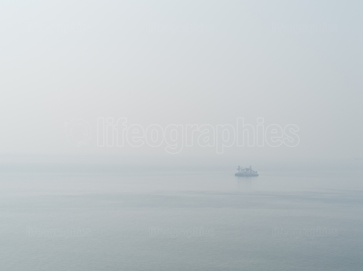 Horizontal sparse pale lonely ship in white ocean background bac