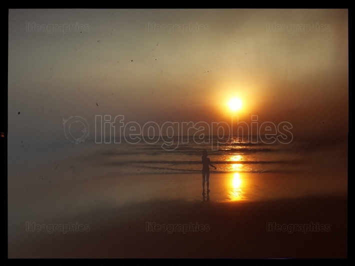 Horizontal vintage indian boy meeting sunset on the beach postca