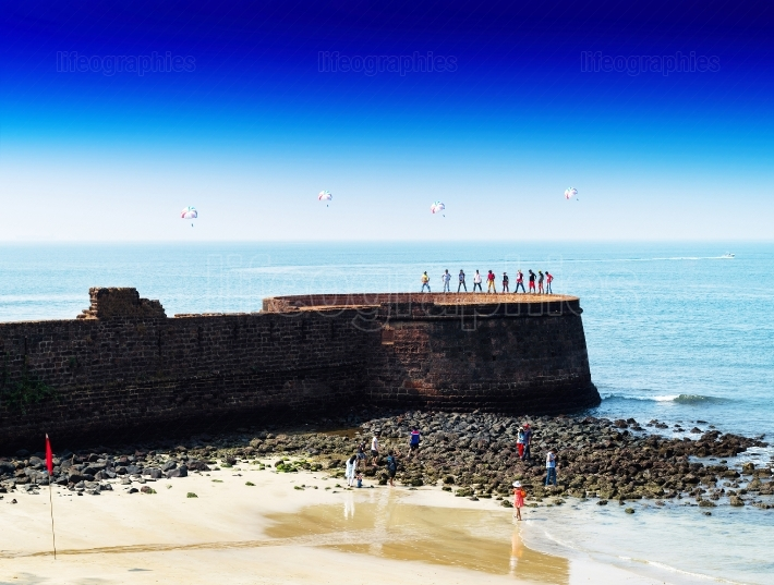 Horizontal vivid Indian castle wall beach with parachutes backgr
