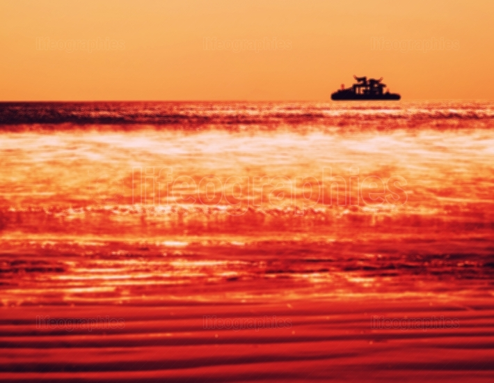 Horizontal vivid orange ship silhouette in ocean blurred backgro