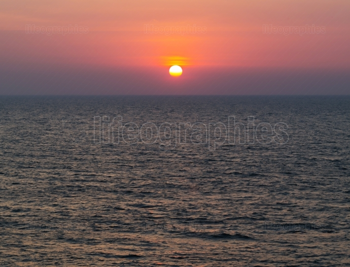 Horizontal vivid vibrant dramatic sunset in Indian ocean backgro