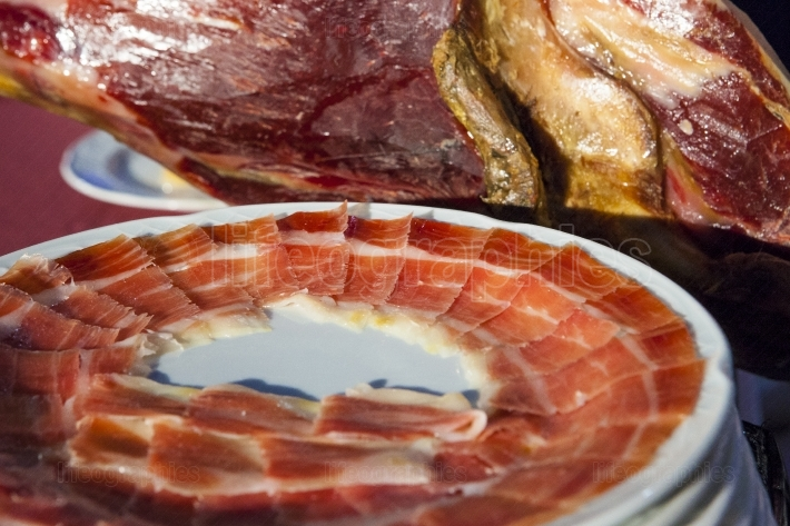 Iberian cured ham with slices plates beside