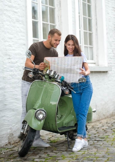 Image of young happy loving couple holding map outdoors near scooter  Looking aside