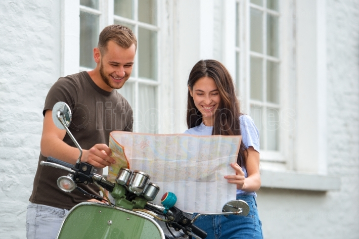 Image of young happy loving couple holding map outdoors near scooter  Looking on map