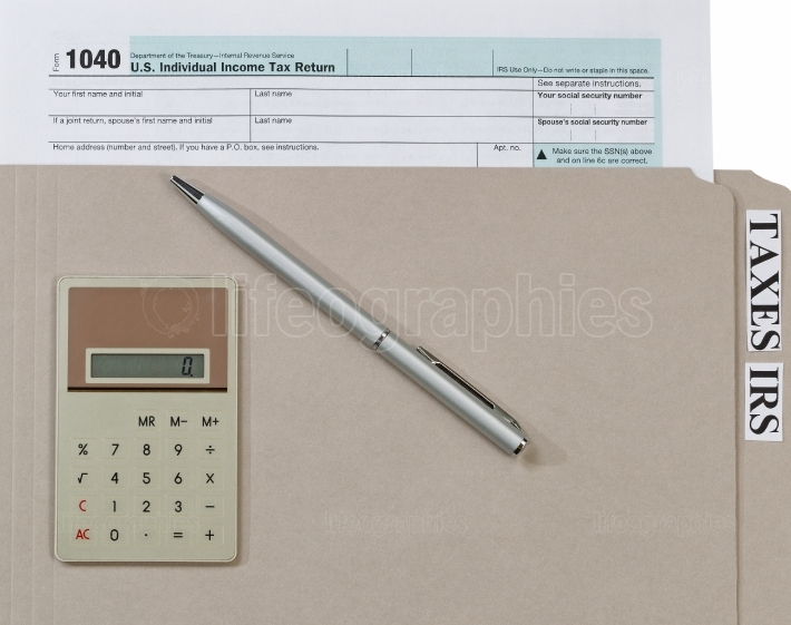 Individual income tax form inside folder with ink pen and calcul