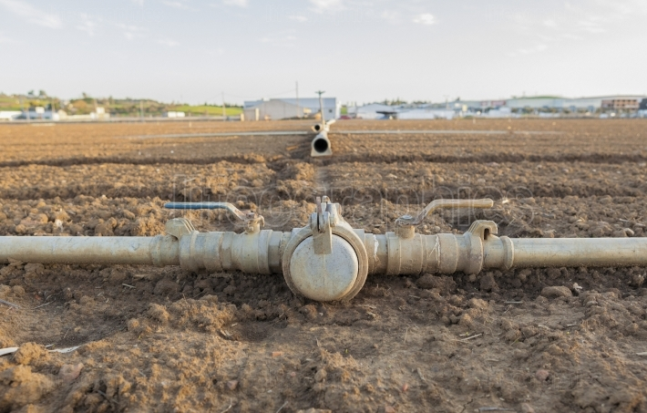 Irrigation metal pipes connections on recently seeded field