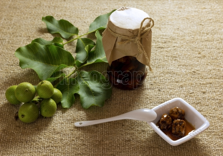 Jam jar nuts on textured burlap with leaves, fruit, white cerami