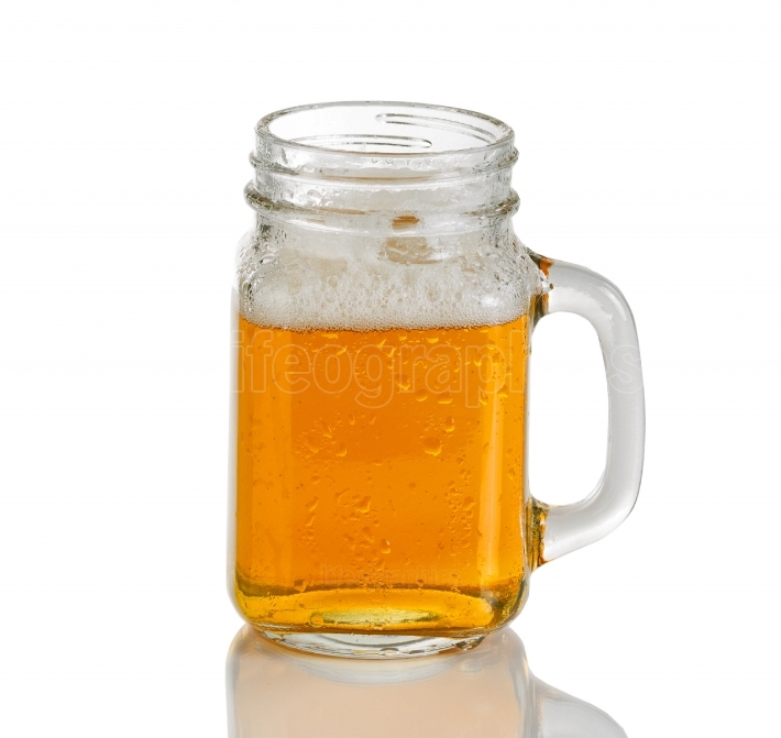 Jar glass filled with cold amber beer on white background