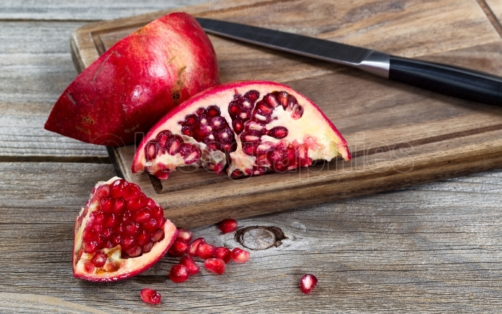 Juicy ripe pomegranates with knife on vintage wood server