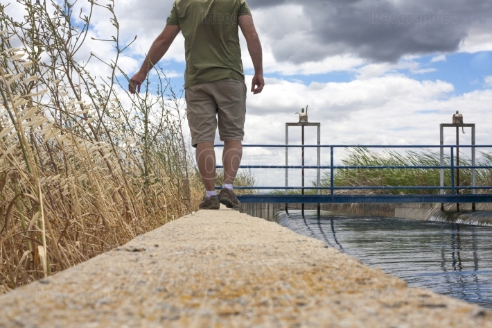 Keeper walking by huge irrigation canal
