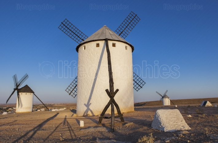 La Mancha windmills with photographer long shadows, Spain