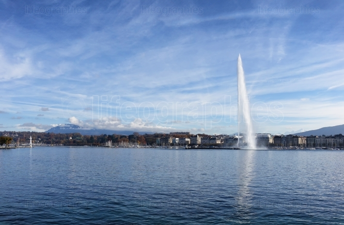 Lake Geneva Switzerland with water fountain and blue sky with cl