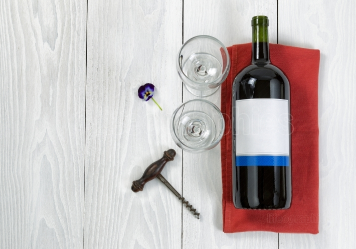 Large bottle of red wine on serving napkin with glasses on white