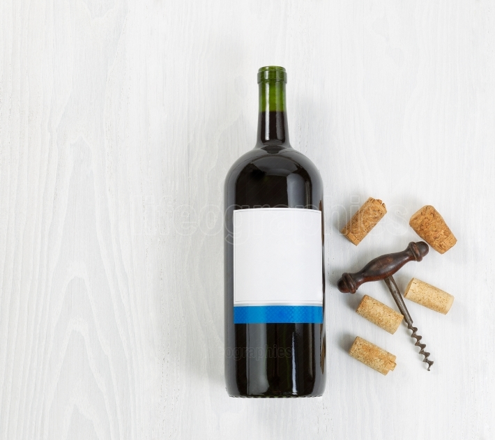 Large bottle of red wine with an antique corkscrew and old corks