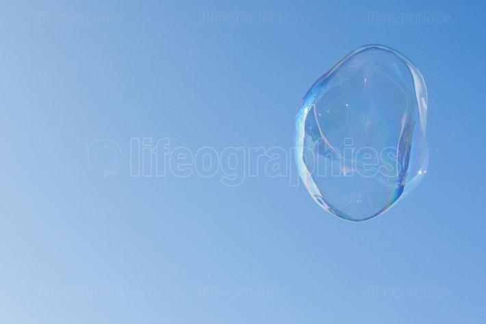 Large Bubble Floats In Air Against Cobalt Blue Sky