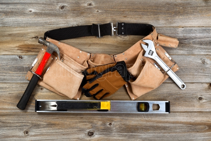 Leather tool belt with tools on rustic wooden boards