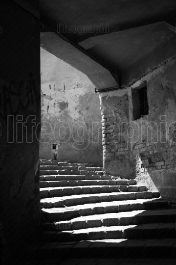 Light flows on the stairs in an empty arched passageway