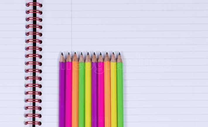Lined up pencil tips on a spiral notebook background