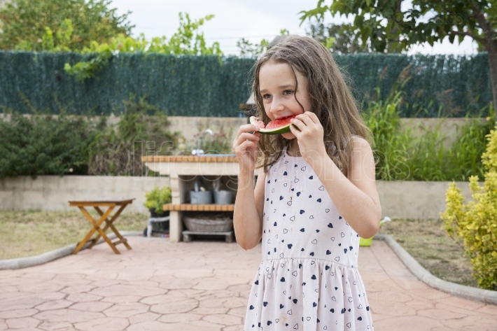 Little blonde girl eating watermelon
