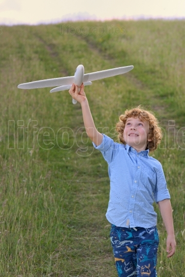 Little boy holding a wooden airplane model
