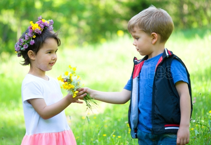 Little boy offering flowers to a little girl