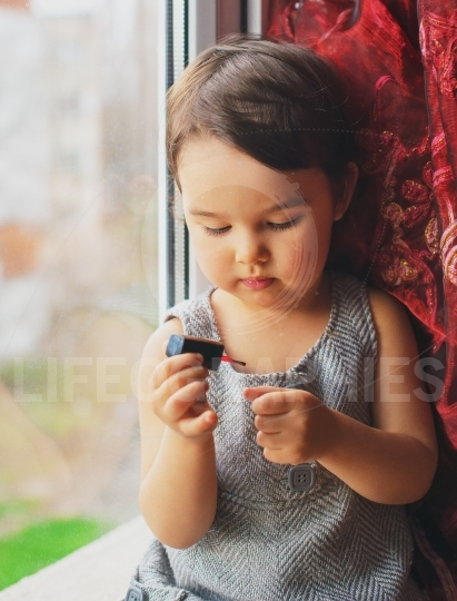 Little child, cute toddler girl having fun playing at home with colorful nail polish doing manicure