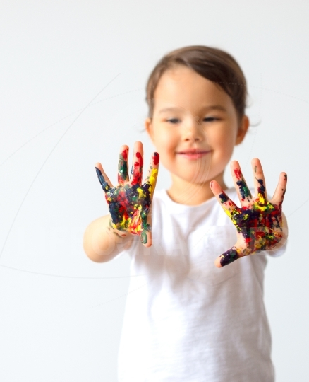 Little child hands painted in colorful paints