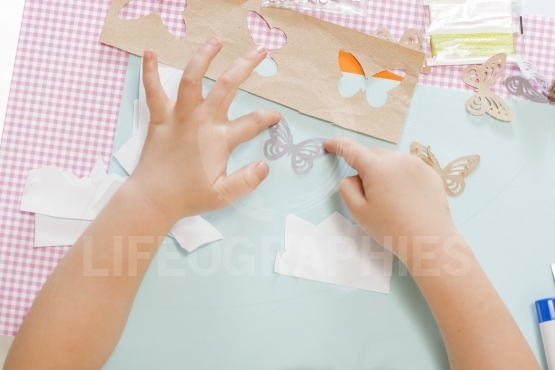 Little child hands sticking butterfly paper on the art lesson class