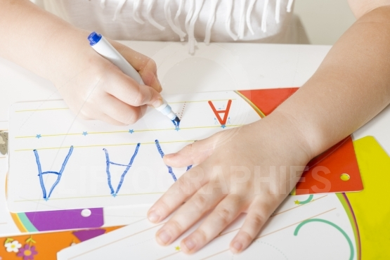Little child hands writing letter A