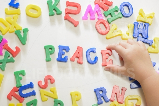 "Little child hands writing word ""peace"" using magnetic letters"
