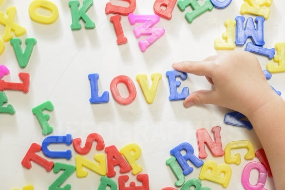 "Little child writing word ""love"" using magnetic letters"