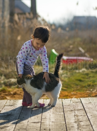 Little Girl and cat play outside