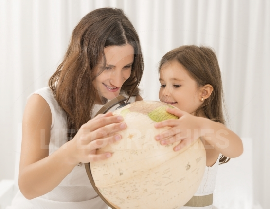 Little girl and her mother looking at a terrestrial globe