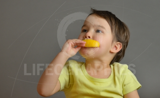 Little girl eating a lemon